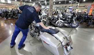 FILE - In this June 26, 2018, file photo, Jason Davis, an employee at the Dillon Brothers Harley Davidson dealership, moves a Street Glide Harley Davidson motorcycle which was sold, at in Omaha, Neb. Harley-Davidson Inc. on Tuesday, April 23, 2019, reported first-quarter earnings of $127.9 million. (AP Photo/Nati Harnik, File)