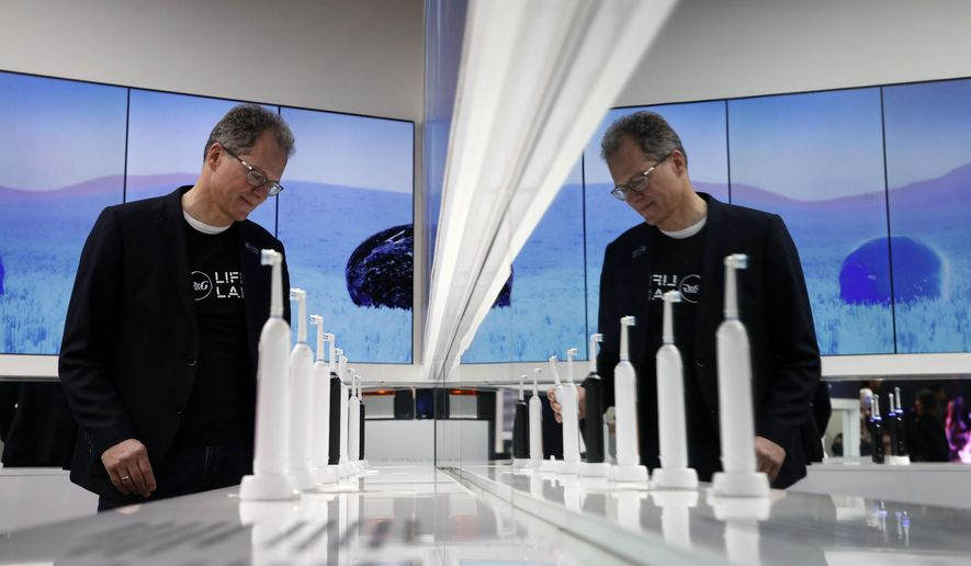 FILE - In this Jan. 7, 2019, file photo a man looks at a display of Oral-B Genius X smart toothbrushes at the Procter & Gamble booth before CES International in Las Vegas. Procter & Gamble Co. reports financial results Tuesday, April 23, 2019. (AP Photo/John Locher, File)