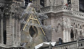 Workers install tarps at Notre Dame cathedral,Tuesday, April 23, 2019 in Paris. The man in charge of the restoration of the fire-ravaged Notre Dame cathedral says he has appointed professional mountain climbers to install temporary tarps over the building to offset potential rain damage. (AP Photo/Thibault Camus)