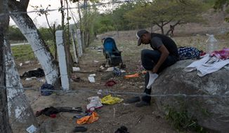 A migrant puts on the socks he'd left behind when his group evaded Mexican immigration agents by running away from the highway and into the brush in Pijijiapan, Chiapas state, Mexico, Monday, April 22, 2019. Mexican police and immigration agents detained hundreds of migrants Monday in the largest single raid on a migrant caravan since the groups started moving through Mexico last year. (AP Photo/Moises Castillo)'