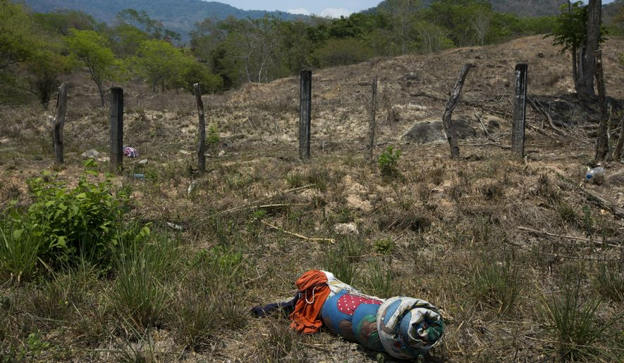 A migrant's bedding lies on the side of the road after after a group of Central American migrants ran away from Mexican immigration agents on the highway through Pijijiapan, Chiapas state, Mexico, Monday, April 22, 2019. Mexican police and immigration agents detained hundreds of migrants Monday in the largest single raid on a migrant caravan since the groups started moving through Mexico last year. (AP Photo/Moises Castillo)