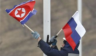 A worker adjusts the flag of Russia and North Korea along the road in Russky Island, off the southern tip of Vladivostok, Tuesday, April. 23, 2019. Preparations are underway for a summit between the leader of North Korea and Russia's president, Russian officials and media reported Tuesday. Russian media have widely reported that the leaders will meet in the port city of Vladivostok on the Pacific Ocean. (Naoya Osato/Kyodo News via AP)