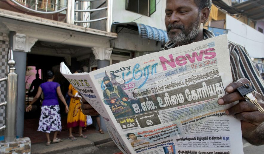 A man reads a newspaper with a lead story on Islamic State taking responsibility of Easter Sunday terror attacks in Colombo, Sri Lanka, Wednesday, April 24, 2019. (AP Photo/Gemunu Amarasinghe)