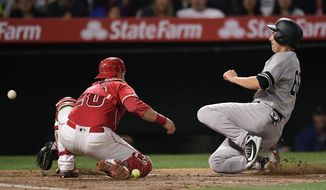 New York Yankees' Kyle Higashioka, right, scores on a sacrifice fly hit by Gleyber Torres as Los Angeles Angels catcher Jonathan Lucroy, left, loses the ball during the third inning of a baseball game Monday, April 22, 2019, in Anaheim, Calif. (AP Photo/Mark J. Terrill)