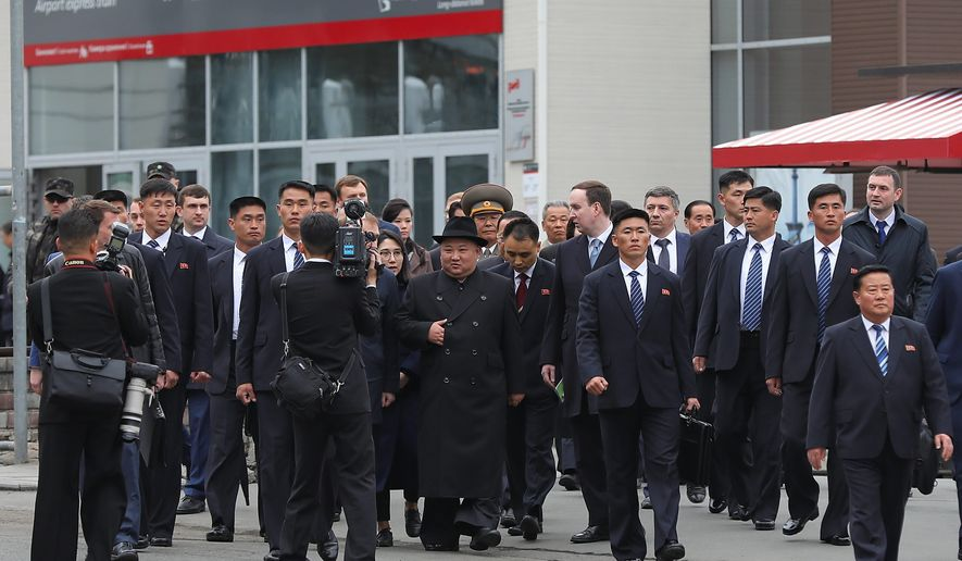 North Korea's leader Kim Jong-un (center) surrounded by Russian and North Korean officials walk after arriving in Vladivostok, Russia, on Wednesday. Mr. Kim arrived for his much-anticipated summit with Russian President Vladimir Putin. (ASSOCIATED PRESS)