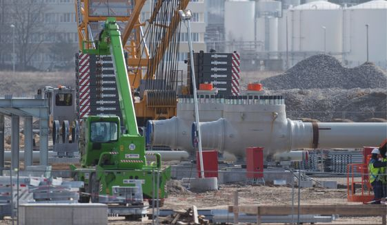 """This March 19, 2019, file photo shows the view of the construction site of the receiving station of the Baltic Sea pipeline """"Nord Stream 2"""" near Mecklenburg-Western Pomerania, Lubmin. The 1,200-kilometer-long gas pipeline will transport around 55 billion cubic meters of Russian natural gas from Russia to Germany every year. The first Russian natural gas is expected to flow through the Nord Stream 2 Baltic Sea pipeline at the end of the year. So far, a third of the cables have been laid. Work in Germany is concentrated on the landing site near Lubmin. (Photo by: Stefan Sauer/picture-alliance/dpa/AP Images)"""