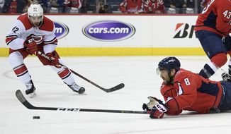Washington Capitals left wing Alex Ovechkin (8), of Russia, reaches for the puck against Carolina Hurricanes center Greg McKegg (42) during the second period of Game 7 of an NHL hockey first-round playoff series, Wednesday, April 24, 2019, in Washington. (AP Photo/Nick Wass)