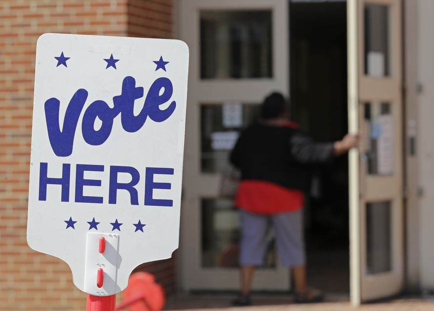 In this file photo, a polling worker enters a polling place in Charlotte, N.C., Wednesday, April 24, 2019 as early voting began in a GOP primary for a special election. (AP Photo/Chuck Burton)  **FILE**