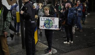 A young Extinction Rebellion climate change protester holds a banner as they briefly block a road in central London, Wednesday, April 24, 2019. The non-violent protest group, Extinction Rebellion, is seeking negotiations with the government on its demand to make slowing climate change a top priority. (AP Photo/Matt Dunham)