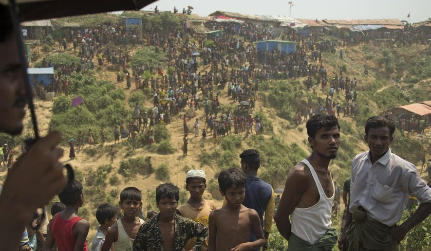 Rohingya refugees watch as firefighters douse flames at the Kutupalong refugee camp in Cox's Bazar, Bangladesh, Wednesday, April 24, 2019. A fire raced through a sprawling camp of Rohingya refugees in southern Bangladesh, destroying more than two dozen huts and a mosque on Wednesday, an official said. (AP Photo)