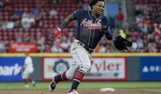 Atlanta Braves' Ronald Acuna Jr. runs home to score on an error by Cincinnati Reds right fielder Yasiel Puig (66) in the fifth inning of a baseball game, Wednesday, April 24, 2019, in Cincinnati. (AP Photo/John Minchillo)