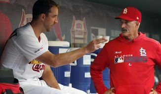 St. Louis Cardinals starting pitcher Adam Wainwright, left, talks with pitching coach Mike Maddux after working the sixth inning of a baseball game against the Milwaukee Brewers Wednesday, April 24, 2019, in St. Louis. (AP Photo/Jeff Roberson)