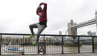 Britain's Mo Farah leaps as he poses for the media during a photo call for the London Marathon in London, Wednesday, April 24, 2019. Farah will take part in the 39th London Marathon which takes place Sunday April 28. (AP Photo/Alastair Grant)