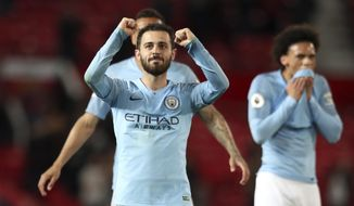 Manchester City's Bernardo Silva and Leroy Sane, right, celebrate at the end of the English Premier League soccer match between Manchester United and Manchester City at Old Trafford Stadium in Manchester, England, Wednesday April 24, 2019. Manchester City won 2-0. (AP Photo/Jon Super)