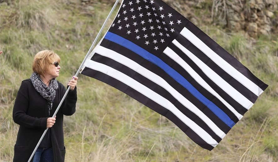 Sheri Hatley of Oakesdale, Wash., waves a flag during a procession of law-enforcement vehicles leaving Colfax, Wash., on Tuesday, April 23, 2019, for a memorial service for Cowlitz County Sheriff's Deputy Justin DeRosier in Portland, Ore. DeRosier was fatally shot on April 13. Hatley's son is Coeur d'Alene, Idaho, police officer Charles Hatley, who recovered after being shot while on duty in Feb., 2018. (Geoff Crimmins/The Moscow-Pullman Daily News via AP)
