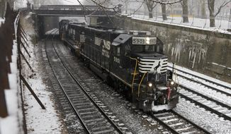 FILE- In this March 3, 2019, file photo a Norfolk Southern freight train passes through the Northside of Pittsburgh. The Norfolk Southern Railway reports earnings Wednesday, April 24. (AP Photo/Gene J. Puskar, File)