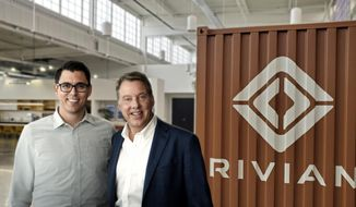 In this undated photo provided by VarnHagen Creative Photo LLC,  RJ Scaringe, Rivian founder and CEO, and Ford Executive Chairman Bill Ford pose for a photo in Dearborn, Mich. Ford announced Wednesday, April 24, 2019, that it is sinking a half-billion dollars into electric vehicle startup Rivian in a deal that has the companies working together on a new Ford electric vehicle based on Rivian underpinnings. (Sam VarnHagen/VarnHagen Creative Photo LLC via AP)