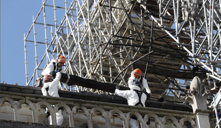 Workers install protections on Notre Dame Cathedral Wednesday, April 24, 2019, in Paris. Professional mountain climbers were hired to install synthetic, waterproof tarps over the gutted, exposed exterior of Notre Dame Cathedral, as authorities raced to prevent further damage ahead of storms that are rolling in toward Paris. (AP Photo/Thibault Camus)