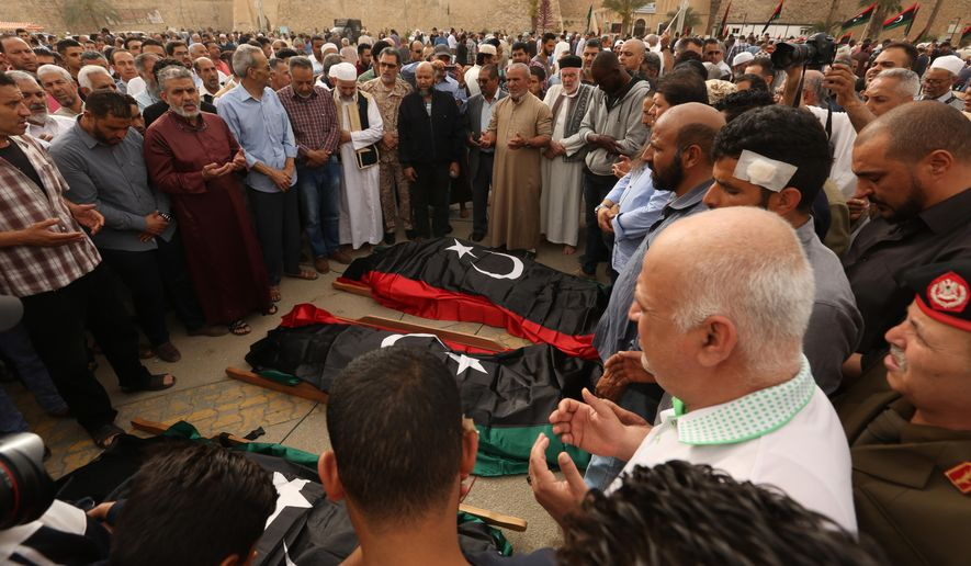 Mourners gather for funeral prayers for fighters killed by warplanes of Field Marshal Khalifa Hifter's forces, Wednesday, April 24, 2019 in Tripoli, Libya. A top Russian diplomat has called on the self-styled Libyan National Army to cease fire and stop its advance on the Libyan capital.(AP Photo/Hazem Ahmed)
