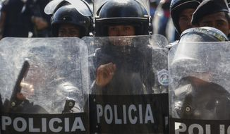 Police block anti-government protesters from marching in Managua, Nicaragua, Wednesday, April 17, 2019. Police prevented the march to commemorate a year since Nicaraguan protesters took to the streets to oppose the government of President Daniel Ortega. (AP Photo/Alfredo Zuniga)
