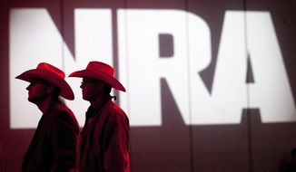 FILE - In this May 4, 2013, file photo, National Rifle Association members listen to speakers during the NRA's 142 annual Meetings and Exhibits at the George R. Brown Convention Center in Houston. The National Rifle Association is suing Los Angeles over a new law requiring companies that want city contracts to disclose whether they have ties to the gun rights group. The lawsuit filed Wednesday, April 24, 2019, claims the law violates the NRA's First Amendment right to free speech and association and its 14th Amendment right to equal protection. (Johnny Hanson/Houston Chronicle via AP, File)