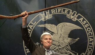 """FILE - In this May 20, 2000, file photo, NRA president Charlton Heston holds up a musket as he tells the 5000 plus members attending the 129th Annual Meeting & Exhibit in Charlotte, N.C., that they can have his gun when they pry it """"from my cold dead hands, """" The ending to his speech drew a standing ovation. (AP Photo/Ric Feld, File)"""