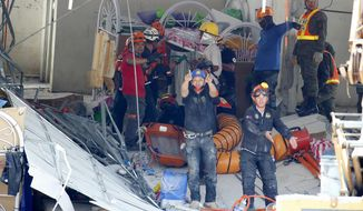 Rescuers gesture to clear the way following the discovery of another survivor in Monday's magnitude 6.1 earthquake that caused the collapse of a commercial building in Porac township, Pampanga province north of Manila, Philippines Tuesday, April 23, 2019. A strong earthquake struck the northern Philippines Monday trapping some people in a collapsed building, damaged an airport terminal and knocked out power in at least one province, officials said. (AP Photo/Bullit Marquez)