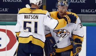 Nashville Predators' Austin Watson (51) taps goaltender Pekka Rinne, right, on the shoulder as they stand by the bench following their 2-1 overtime loss to the Dallas Stars in Game 6 of an NHL hockey first-round playoff series in Dallas, Monday, April 22, 2019. (AP Photo/Tony Gutierrez)