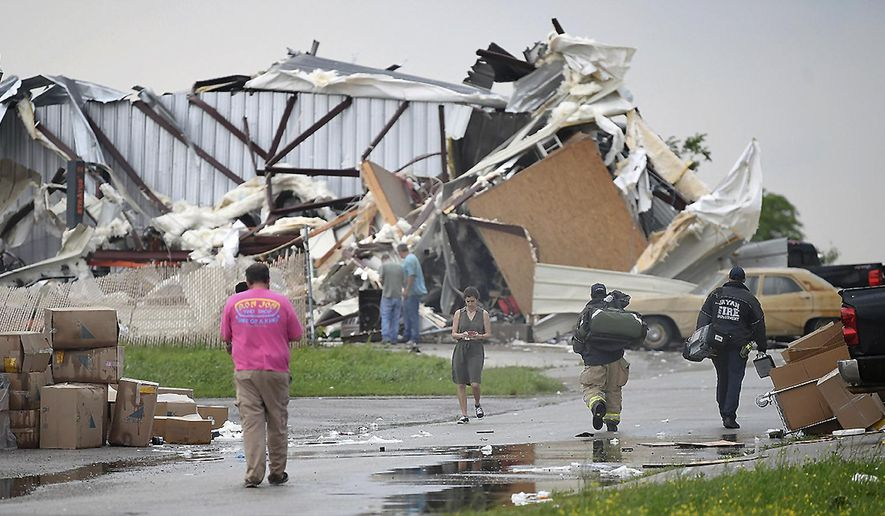 Victims and rescue personnel walk in the ruins left by strong winds that hit a business area in rural Bryan, Texas, Wednesday, April 24, 2019. Hail and damaging winds are forecast from San Antonio to South Texas.  (Dave McDermand/College Station Eagle via AP)
