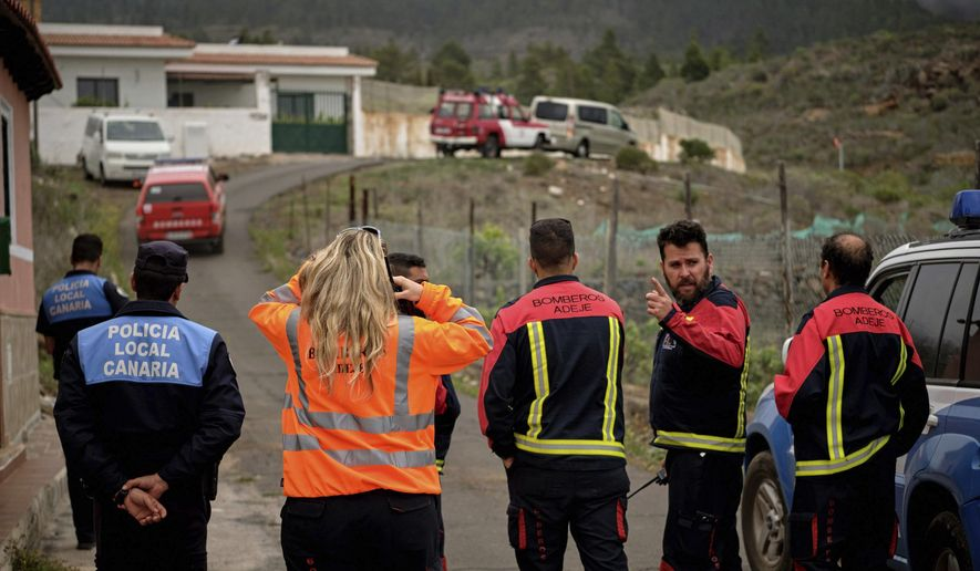 Members of an emergency team stand on a road leading to a cave at the base of the Teide volcano, where a mother and son were found in Santa Cruz de Tenerife in the Canary Islands, Spain, Wednesday, April 24, 2019. The bodies of a German woman and her 10-year-old son were found in a cave in the Canary island of Tenerife, on Wednesday said the Civil Guard, adding that the boy's father, who was also German, had been arrested. (AP Photo/Andres Gutierrez)