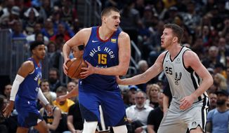 Denver Nuggets center Nikola Jokic (15) is pressured by San Antonio Spurs center Jakob Poeltl (25) in the first half of Game 5 of an NBA basketball first round playoff series, Tuesday, April 23, 2019, in Denver. (AP Photo/David Zalubowski)