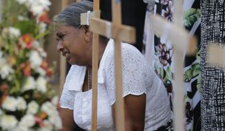 An elderly Sri Lankan woman cries sitting next to the grave of her family member who died in a Easter Sunday church explosion in Katuwapitiya village in Negombo, Sri Lanka, Wednesday, April 24, 2019. Sri Lanka's president has asked for the resignations of the defense secretary and national police chief, a dramatic internal shake-up after security forces shrugged off intelligence reports warning of possible attacks before Easter bombings that killed over 350 people, the president's office said Wednesday. (AP Photo/Eranga Jayawardena)
