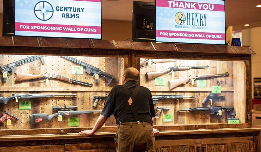 A man looks at cases of firearms in the halls of the Indianapolis Convention Center on Thursday where members of the National Rifle Association will be holding its 148th annual meetings in Indianapolis. The group's meetings come at a tumultuous time within the gun-rights organization. (Associated Press photographs)