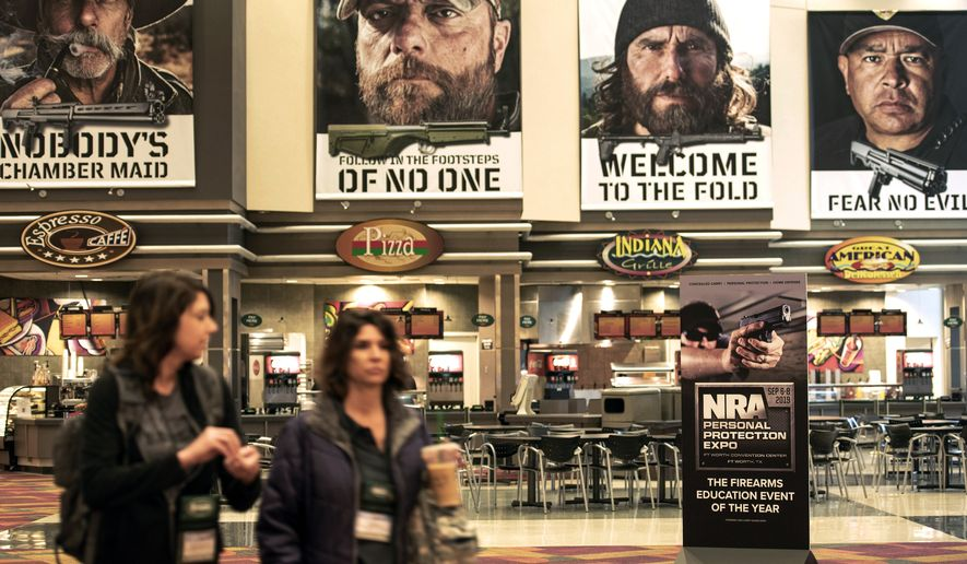 Posters are displayed on the walls of the Indianapolis Convention Center on Thursday, April 25, 2019, where members of the National Rifle Association will be holding its 148th annual meetings in Indianapolis. The group's meetings come at a tumultuous time within the gun-rights organization. (AP Photo/Lisa Marie Pane)