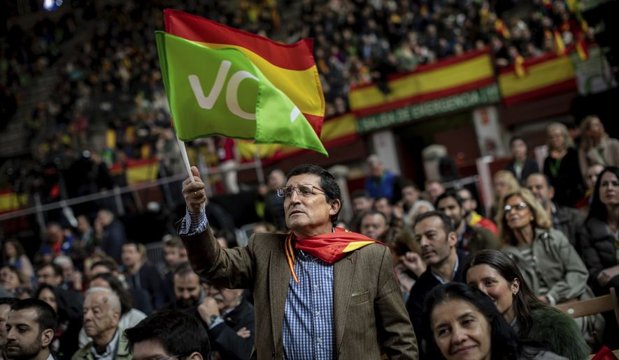 In this Saturday, April 6, 2019, photo, a supporter of Spain's far-right Vox Party waves the Spanish and VOX flag during a party event in Leganes, outskirts of Madrid, Spain. A substantial pool of undecided voters and a right-wing splintered by a rising populist party are making confident predictions harder to come by as Spain prepares for its third parliamentary election in less than four years. (AP Photo/Bernat Armangue) ** FILE **
