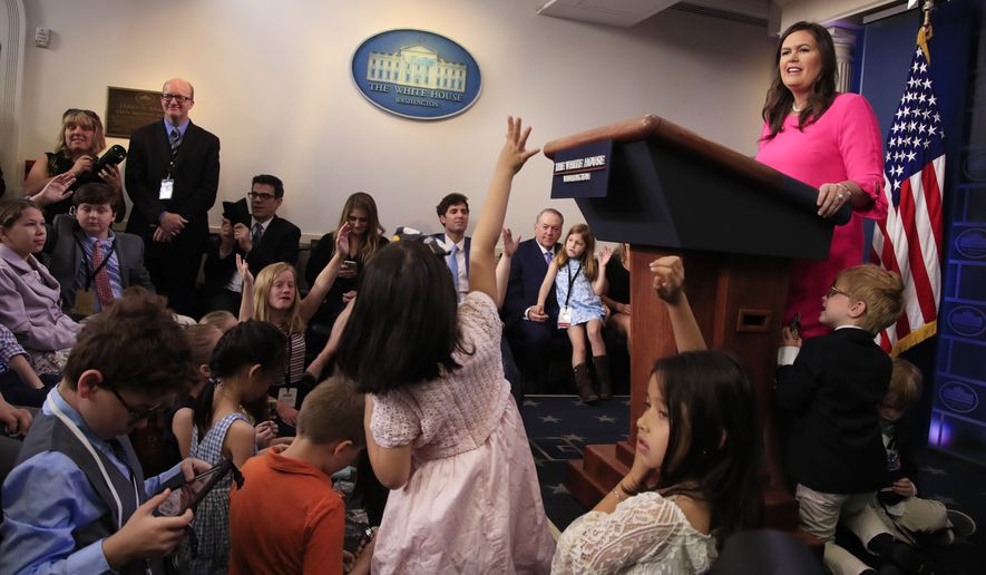 White House press secretary Sarah Huckabee Sanders with her children Huck Sanders, with eye glasses, and George Sanders, conducts a briefing for children of journalists and White House staff in the Brady press briefing room at the White House in Washington, Thursday, April 25, 2019, to commemorate Take Our Daughters and Sons to Work Day. (AP Photo/Manuel Balce Ceneta)