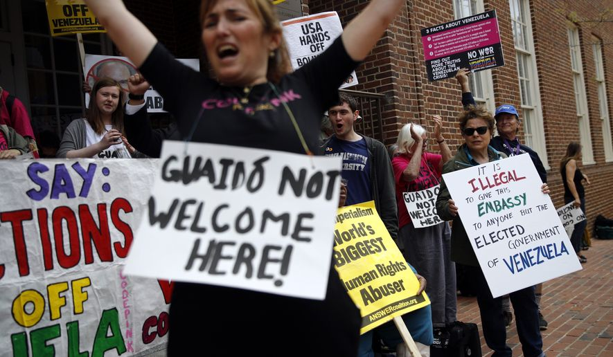 Protesters against Juan Guiado, opposition leader and self-proclaimed interim president of Venezuela, chant outside the Venezuelan Embassy, Thursday, April 25, 2019, in Washington. Activists are occupying the embassy to prevent representatives of Guiado from taking over the building. (AP Photo/Patrick Semansky)