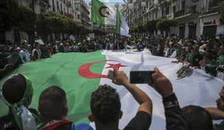 "FILE - In this April 12, 2019 file photo, protestors carry a large flag and chant slogans during a demonstration against the country's leadership, in Algiers. Algerian authorities are leading a ""clean hands"" campaign aimed at rooting out corruption that has caught up top tycoons and former government ministers. Corruption is one of the major complaints of the masses of protesters who helped drive longtime leader Abdelaziz Bouteflika from office earlier this month. (AP Photo/Mosa'ab Elshamy, File)"