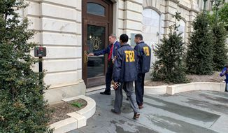 Federal Bureau of Investigation and Internal Revenue Service agents enter City Hall in Baltimore, MD., on Thursday, April 25, 2019. FBI, IRS launched raids connected to Baltimore Mayor Catherine Pugh amid widening probes to determine whether she used sales of her children's books to disguise government kickbacks. (Ian Duncan/The Baltimore Sun via AP)