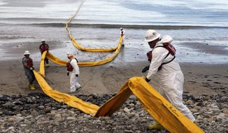 FILE - In this May 21, 2015, file photo, workers prepare an oil containment boom at Refugio State Beach, north of Goleta, Calif., two days after an oil pipeline ruptured, polluting beaches and killing hundreds of birds and marine mammals. A company that caused the worst California coastal oil spill in 25 years has been fined more than $3.3 million. A judge in Santa Barbara issued the fine and penalty Thursday, April 25, 2019, against Houston-based Plains All American Pipeline. Additional damages could be levied at a restitution hearing next month. (AP Photo/Jae C. Hong, File)