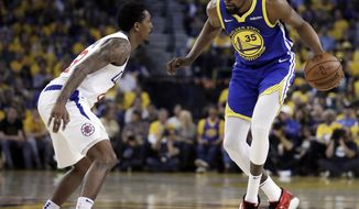 Golden State Warriors' Kevin Durant, right, drives the ball against Los Angeles Clippers' Lou Williams during the first half in Game 5 of a first-round NBA basketball playoff series, Wednesday, April 24, 2019, in Oakland, Calif. (AP Photo/Ben Margot)