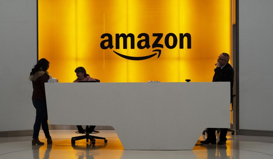 FILE - In this Feb. 14, 2019 file photo, people stand in the lobby for Amazon offices in New York. Amazon.com Inc. reports earns on Thursday, April 25. (AP Photo/Mark Lennihan, File)