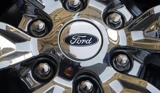 FILE- In this Feb. 14, 2019, file photo a wheel on a 2019 Ford Expedition 4x4 is displayed at the 2019 Pittsburgh International Auto Show in Pittsburgh. Ford Motor Co. reports earns on Thursday, April 25. (AP Photo/Gene J. Puskar, File)
