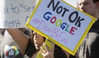 FILE - In this Nov. 1, 2018, file photo, workers protest against Google's handling of sexual misconduct allegations at the company's Mountain View, Calif., headquarters. Google says it has updated the way it investigates misconduct claims, changes it pledged to make after thousands of employees walked out in protest last November. The company says the changes make it simpler for employees to file complaints about sexual misconduct or other harassment. The move follows claims by two walkout organizers that they faced Google retaliation for helping to put together the protest. (AP Photo/Noah Berger, File)