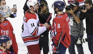Carolina Hurricanes right wing Justin Williams (14) shakes hands with Washington Capitals left wing Alex Ovechkin (8), of Russia, after Game 7 of an NHL hockey first-round playoff series, Wednesday, April 24, 2019, in Washington. The Hurricanes won 4-3 in double overtime. (AP Photo/Nick Wass) ** FILE **