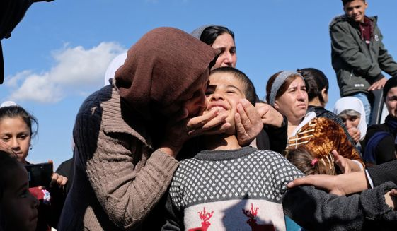 FILE - In this March 2, 2019 file photo, Dilbar Ali Ravu, 10, is kissed by his aunt Dalal Ravu when Yazidi children were reunited with their families in Iraq after five years of captivity with the Islamic State group, at a truck stop on the road between Sinjar and Dohuk, Iraq. The Yazidi community in Iraq said Thursday, April 25, 2019, that it will accept the survivors of the Islamic State group's campaign of enslavement and welcome the children conceived through rape into the minority community. (AP Photo/Philip Issa, File)