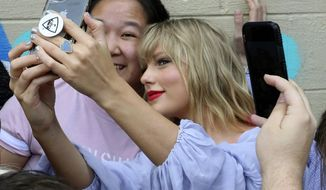Taylor Swift takes a selfie with a fan at an appearance at a butterfly mural in the Gulch in Nashville, Tenn., on Thursday, April 25, 2019. (Alan Poizner/The Tennessean via AP)