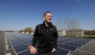 In this April 15, 2019, photo Todd Miller stands next to solar panels on the roof of his solar installation business in Ankeny, Iowa. When Miller began his solar installation business one of the challenges he faced was keeping up with customer orders, as tax incentives and plunging prices for the boxy roof panels created a booming demand for this form of clean energy. Four years later now he faces a real obstacle: action in the state Legislature that he says could put solar companies out of business.(AP Photo/Charlie Neibergall)