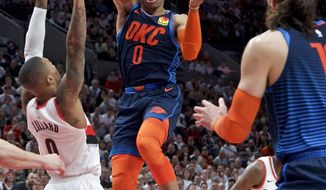 Oklahoma City Thunder guard Russell Westbrook, center, passes the ball away from Portland Trail Blazers guard Damian Lillard during the first half of Game 5 of an NBA basketball first-round playoff series, Tuesday, April 23, 2019, in Portland, Ore. (AP Photo/Craig Mitchelldyer)
