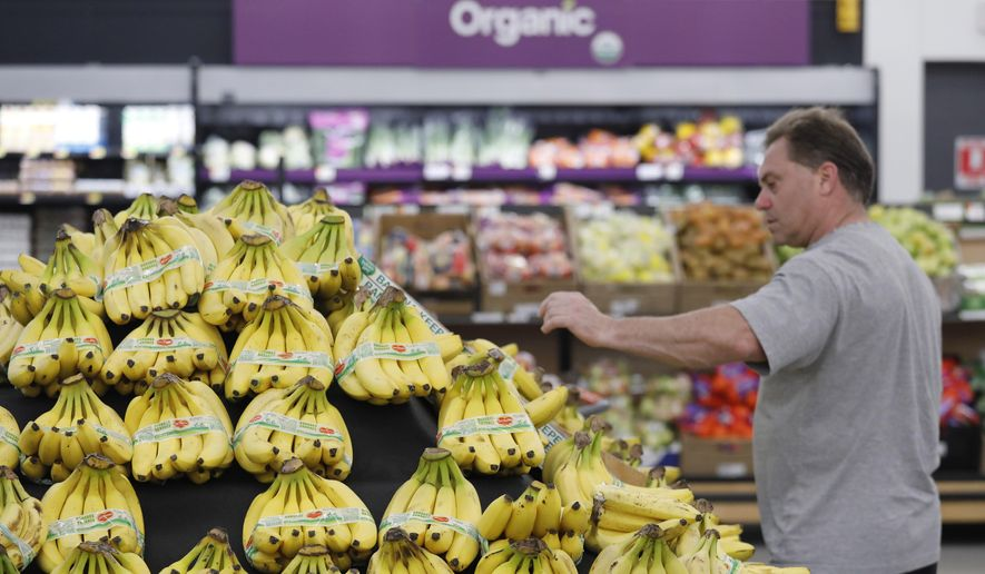 A customer shops for bananas at a Walmart Neighborhood Market, Wednesday, April 24, 2019, in Levittown, N.Y. High-resolution cameras suspended from the ceiling point to the table of bananas and determine from the color of the bananas how ripe they are. When a banana starts to bruise, that would send an alert to an associate to replenish. (AP Photo/Mark Lennihan)